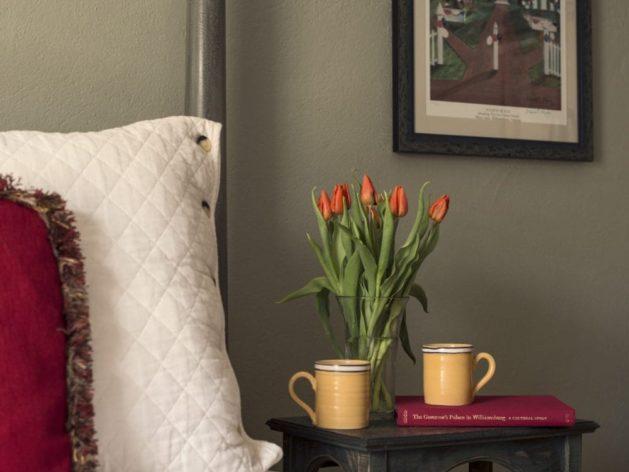 nightstand with 2 mugs and vase of tulips