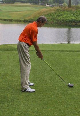 man in orange shirt playing golf