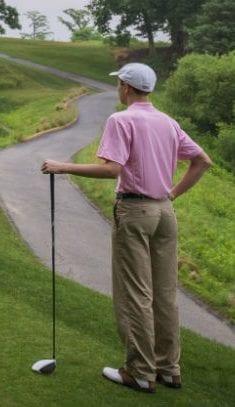man in pink shirt playing golf
